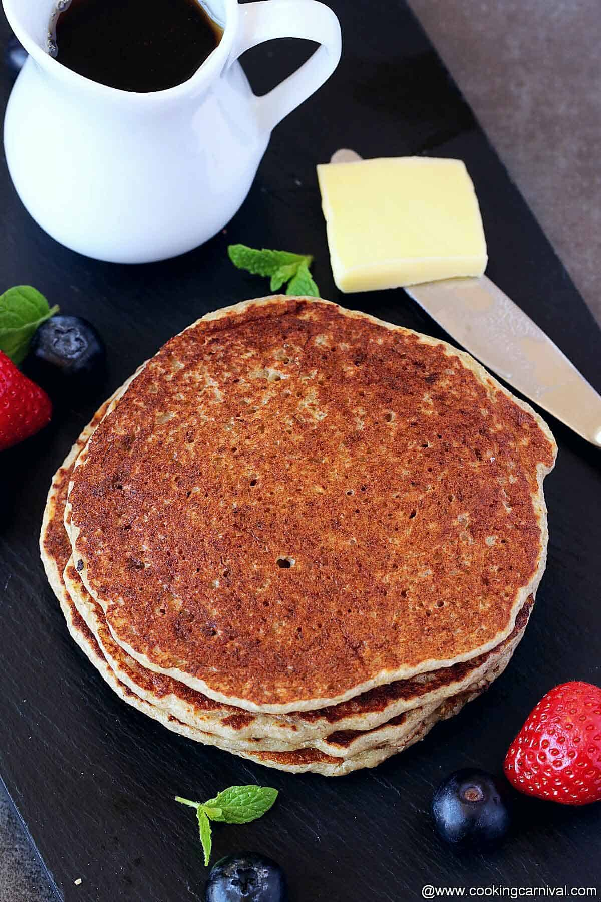 stack of Oatmeal pancake, butter and maple syrup on the sides