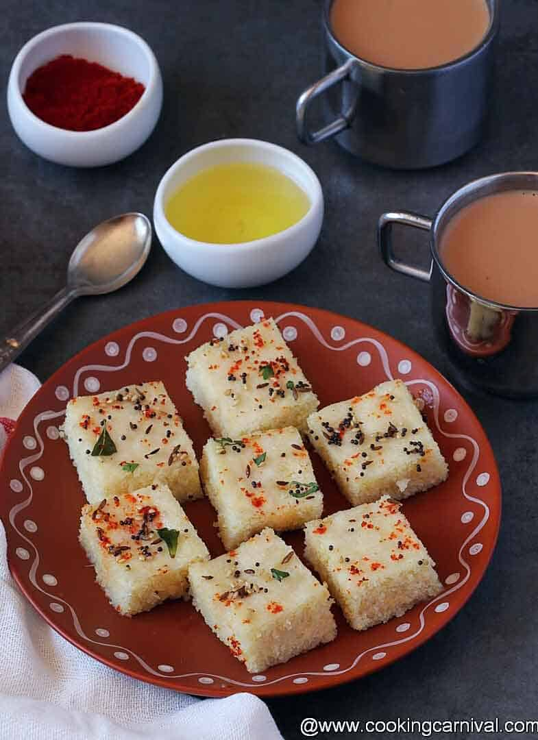Dhokla on a traditional plate, tea, oil and chili powder in sides