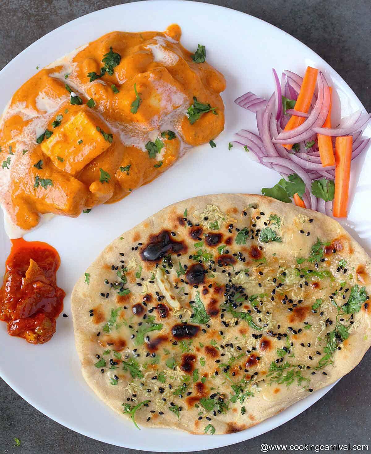 Tandoori garlic roti, kaju paneer, salad and pickle on white plate