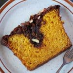 slice of eggless mango cake in a plate with fork