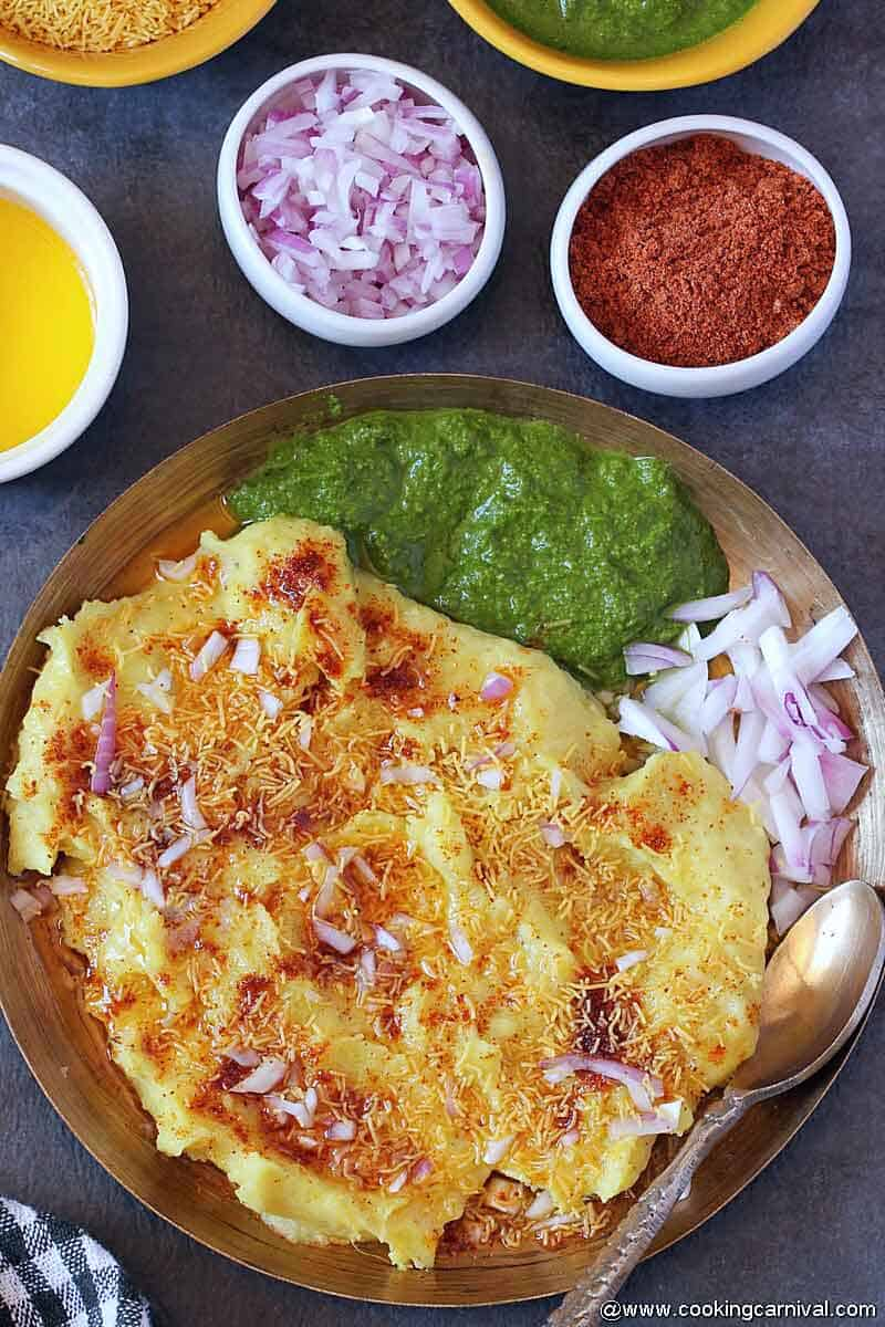 Surti locho in kansa plate, green chutney and onion on the sides