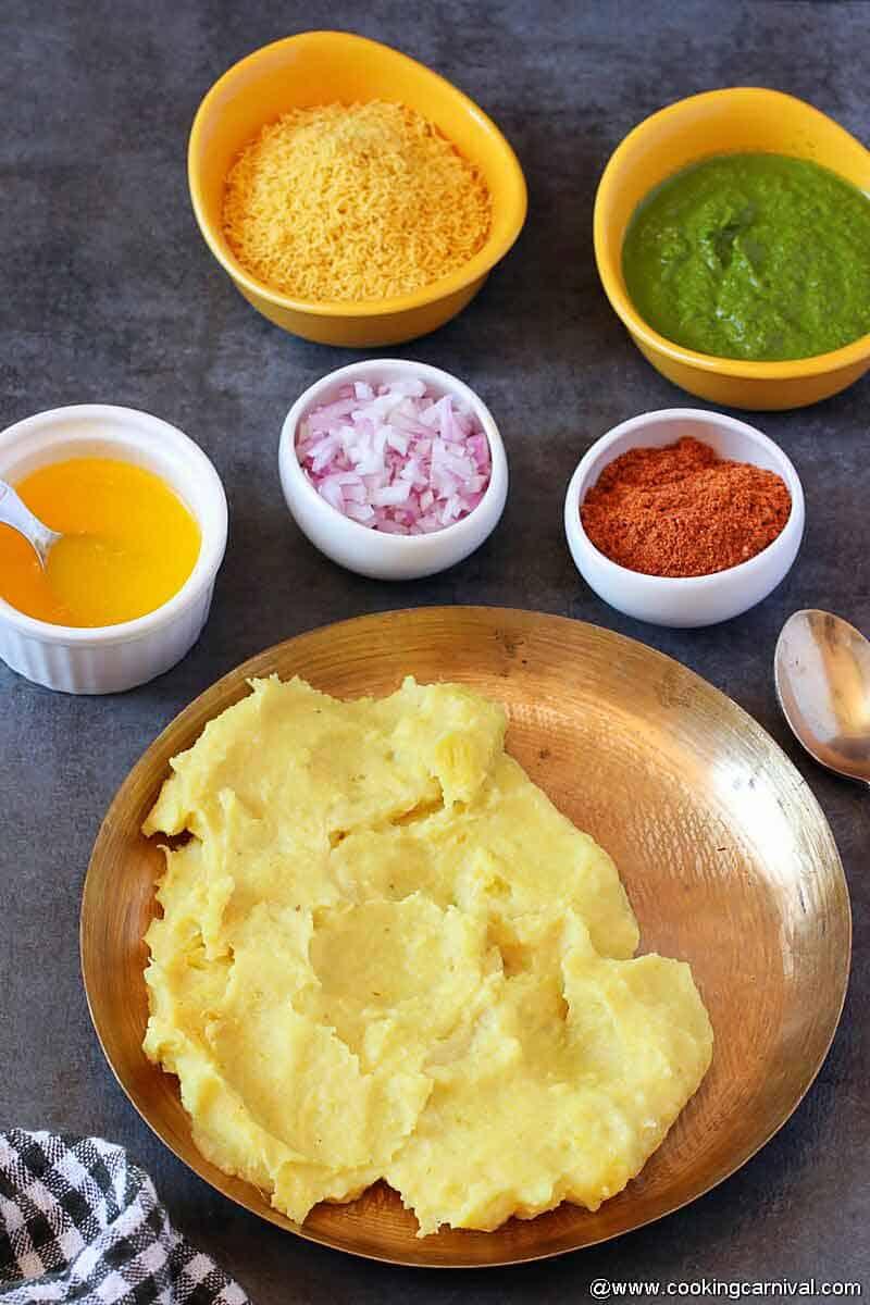 Locho served in kansa plate, butter, onion, sev, masala, green chutney on the sides