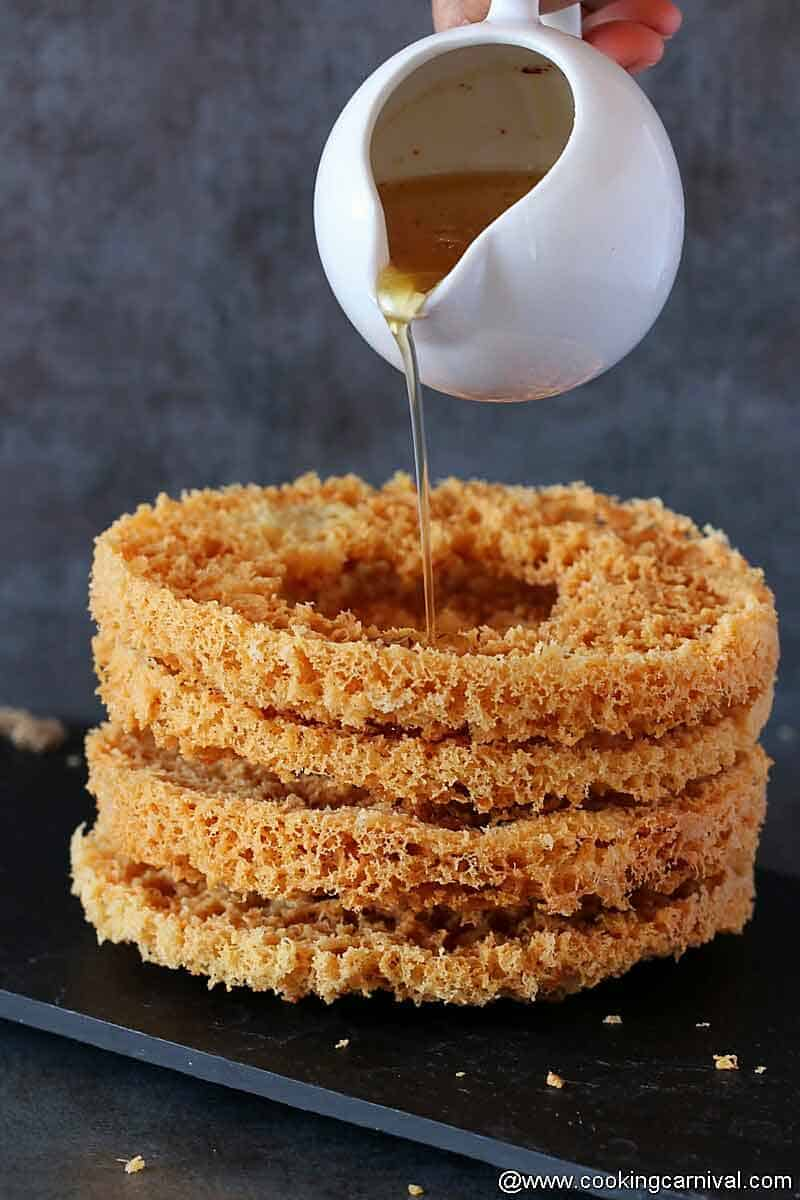 Pouring chasni (Sugar syrup) on stack of ghevar