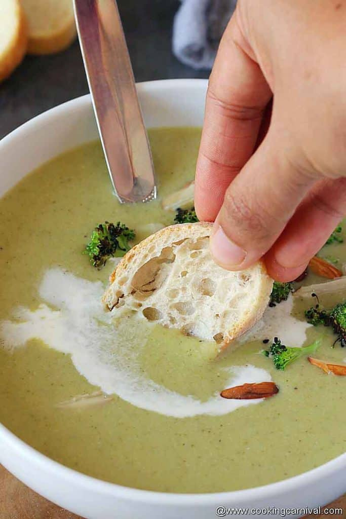 dunking crusty bread in creamy broccoli almond soup