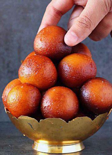 picking gulab jamun from a bowl
