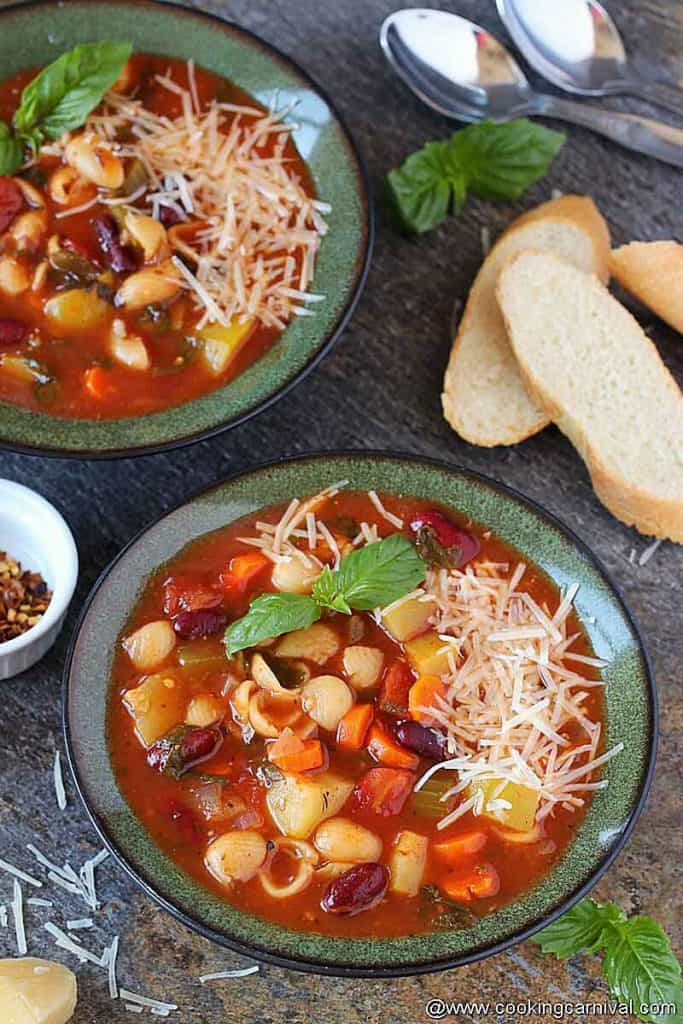 2 bowl bowl full of hearty minestrone soup made in instant pot, crusty bread on the sides.