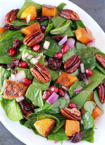 Butternut squash spinach salad on a white plate