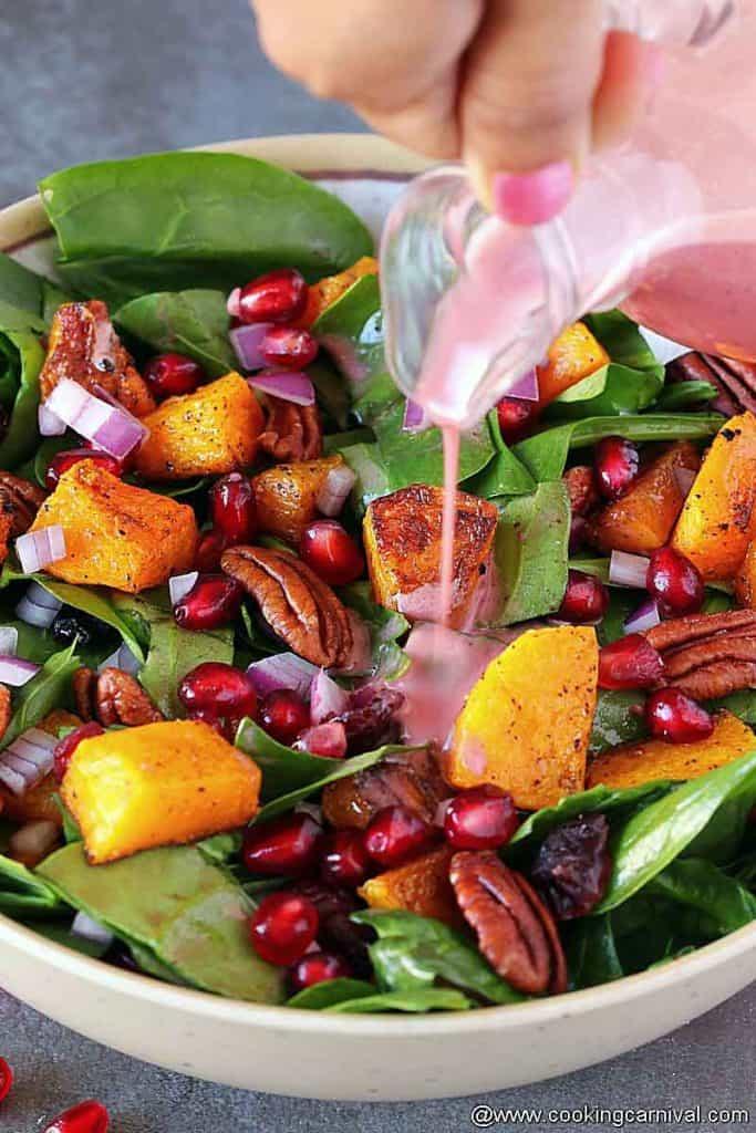 adding pomegranate vinaigrette on a spinach butternut squash salad