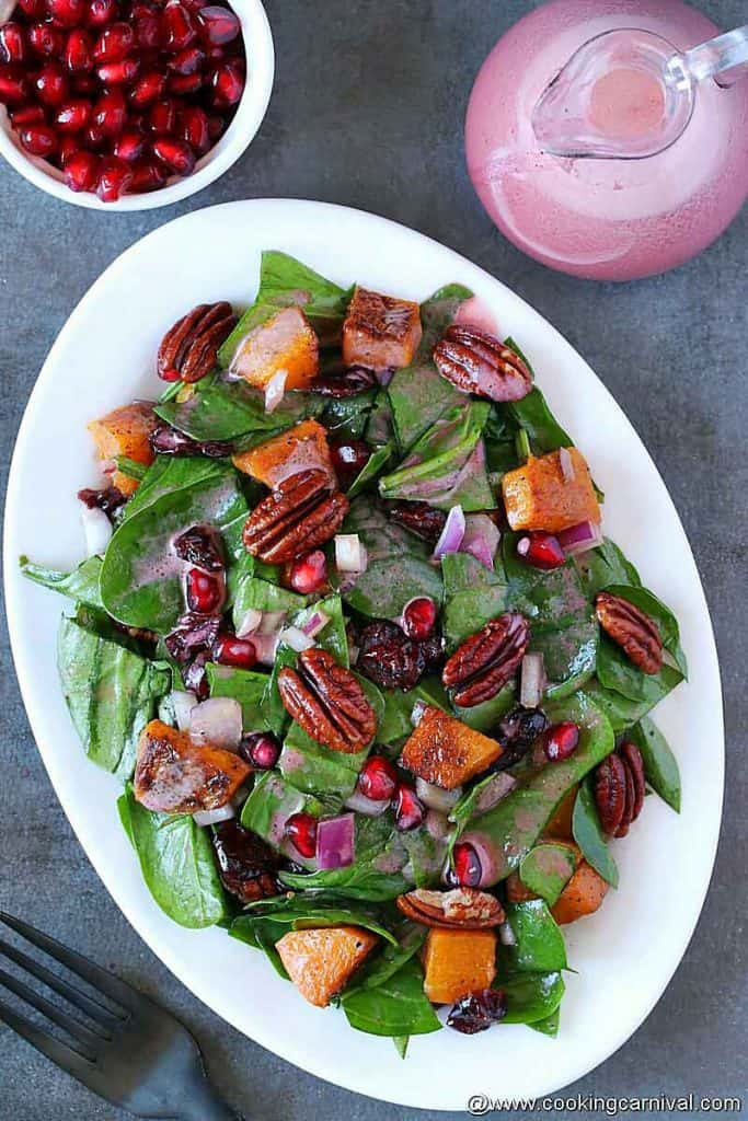Butternut squash spinach salad with pomegranate vinaigrette on a white plate