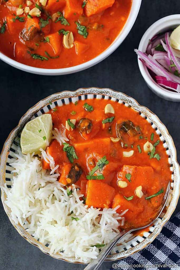Rice and African peanut stew in a white bowl with spoon