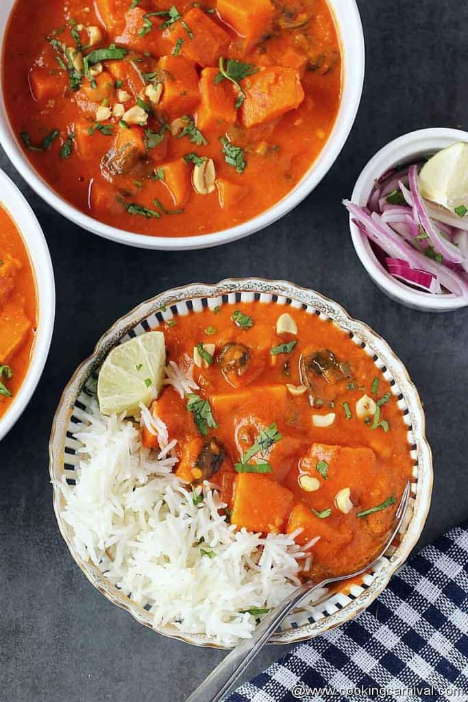 African peanut stew with rice in a bowl, onion, lemon on the side