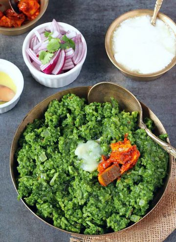 Spinach khichdi in a kansa bowl, served with pickle, ghee and curd