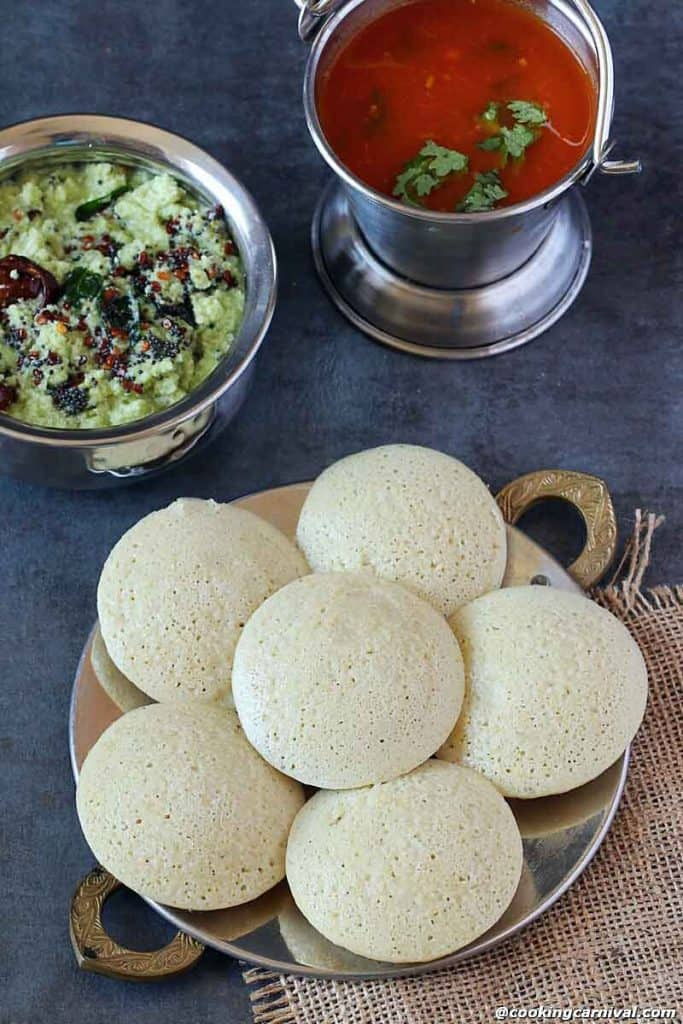 Quinoa idlis in a plate, coconut chutney and tomato rasam on the side