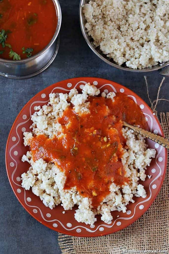 Tomato Rasam qith barnyrd millet on a plate with spoon