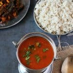 Tomato rasam in steel pot, barnyard millet on the sides
