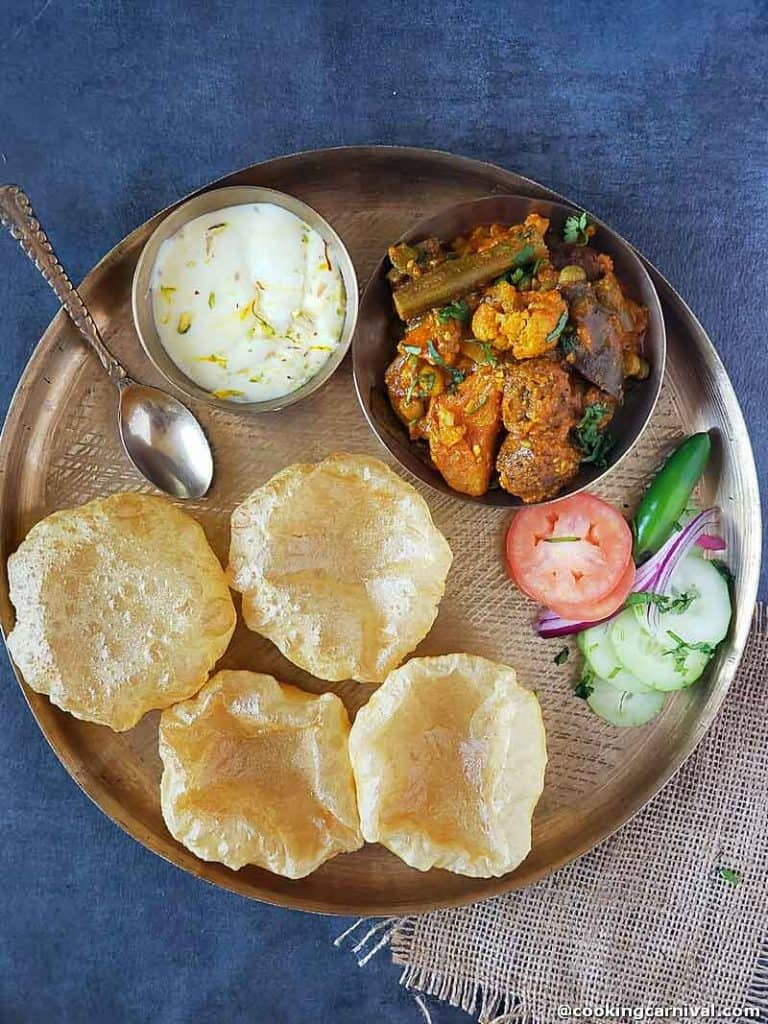 A traditional kathiyadi thali with Undhiyu, poori, shrikhand and salad