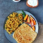 Pnaeer bhiuji, paratha and salad on a plate