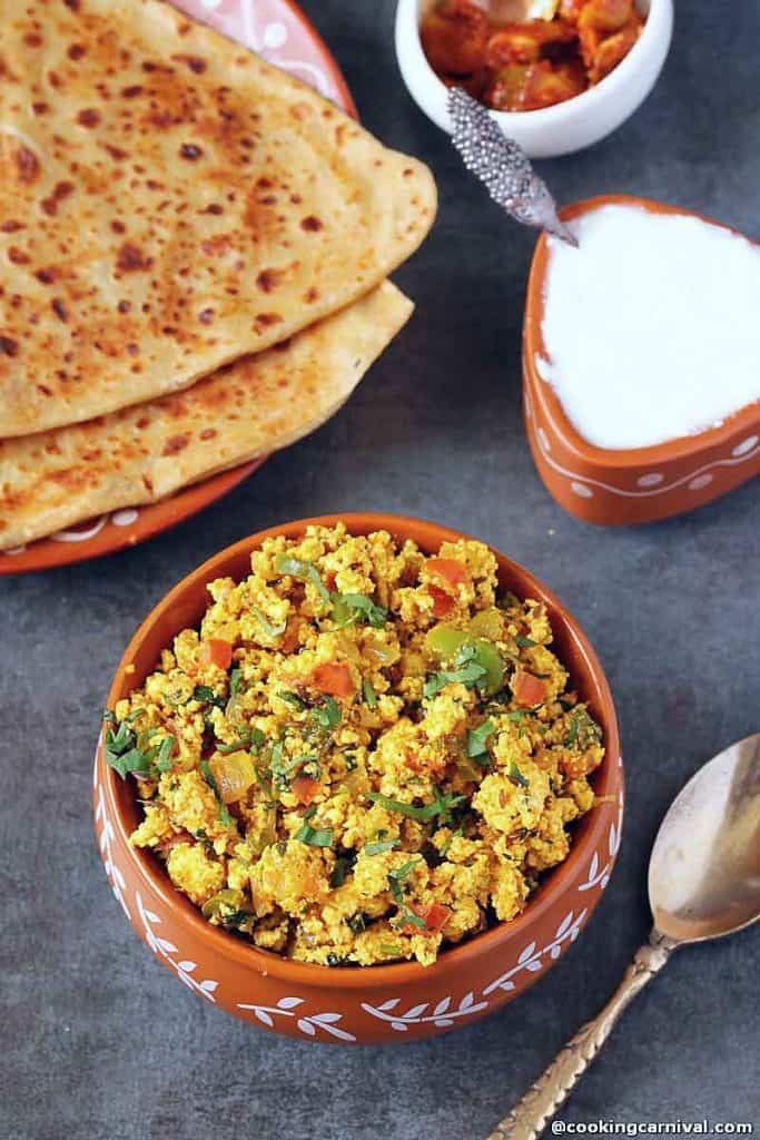 Paneer bhurji in a bowl, paratha, curd nd pickle on the side