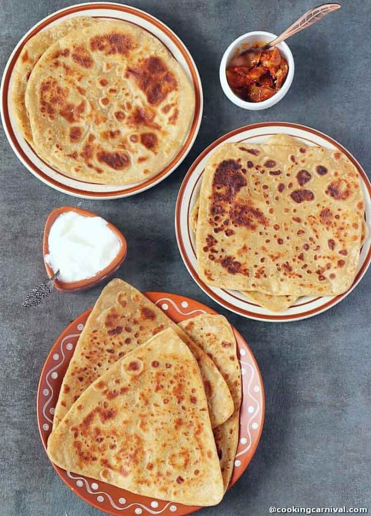 Triangle, square and round whole wheat paratha on black tile