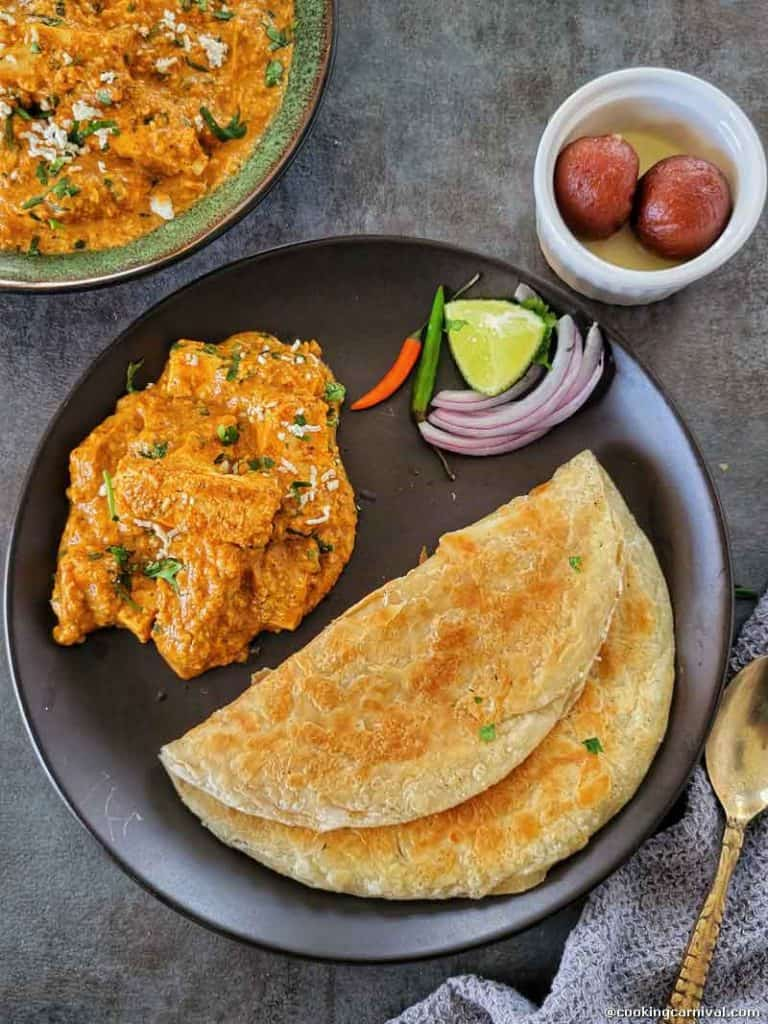 Paneer curry, paratha, onion, chii, gulab jamun and lime on a black plate