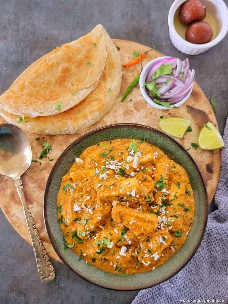 Paneer lababdar in a bowl, paratha, onion, green chilies and lime on the side