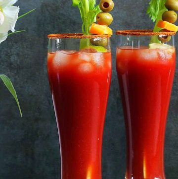 Bloody may virgin drink in 2 tall glasses, garnished with celery, olives, cheese