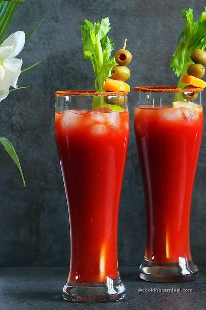 Virgin Bloody Mary drink in 2 tall glasses, garnished with celery, olives, lime and cheese