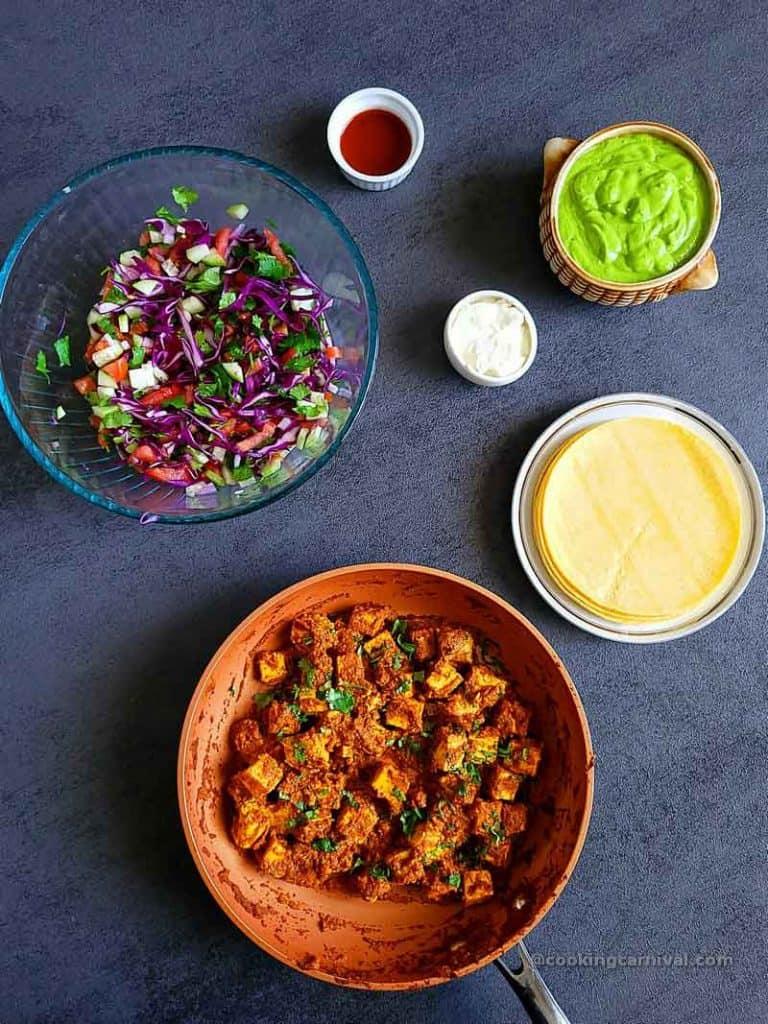 achari paneer, tacos topping and corn tortilla on a gray table