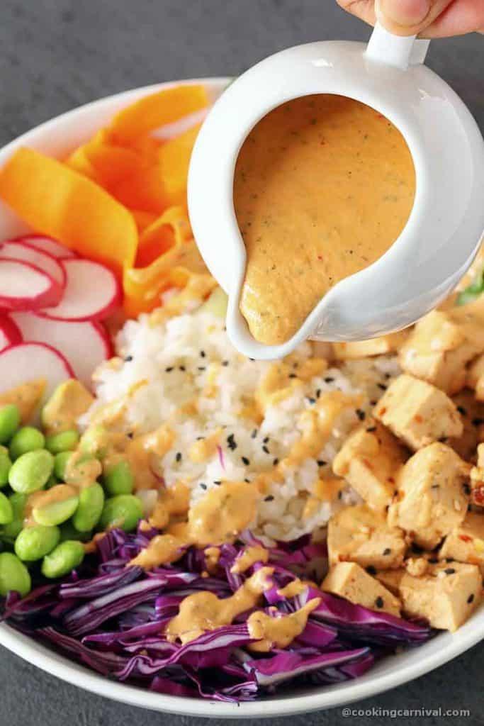 drizzling chipotle tahini sauce over vegan poke bowl