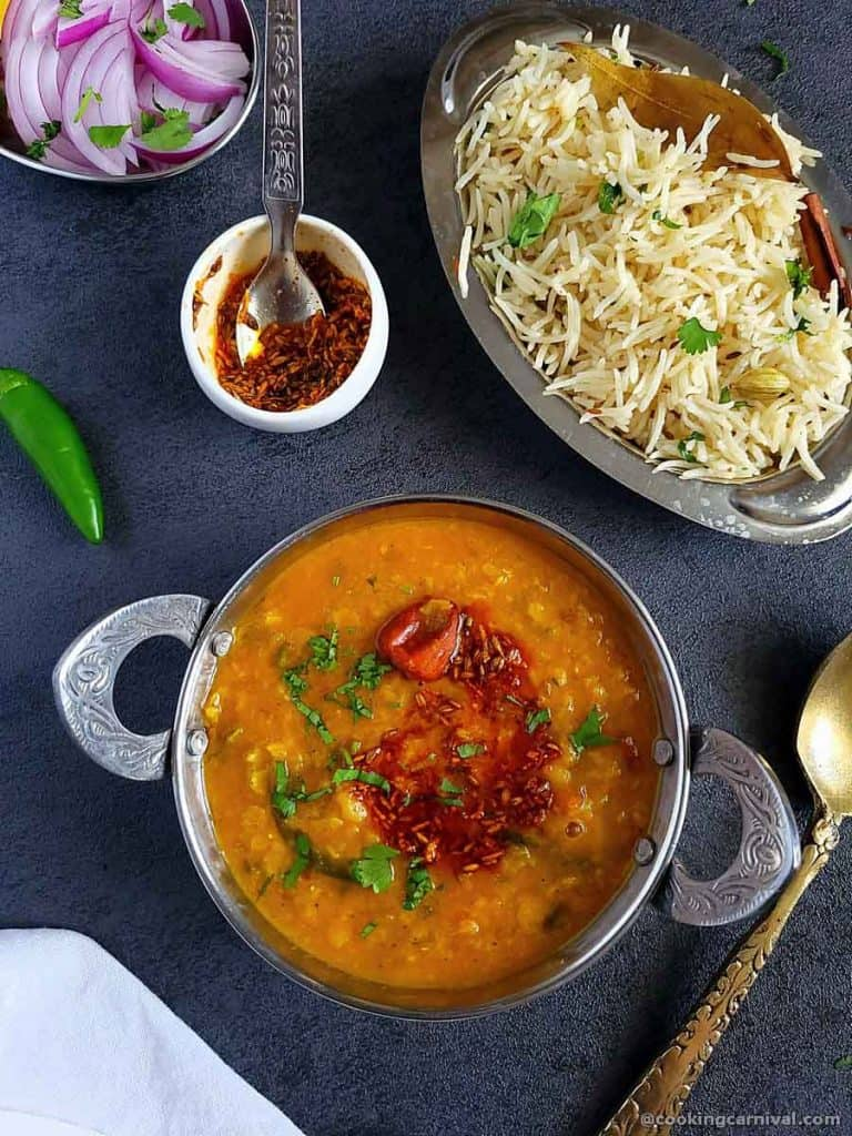 Dal tadka in steel bowl, jeera rice and onion on the sides