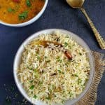 Jeera rice in a white bowl, dal tadka on side