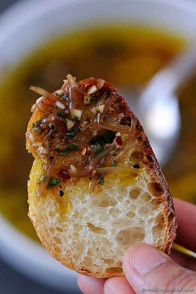 Close up shot of bread dipped on olive oil and herbs