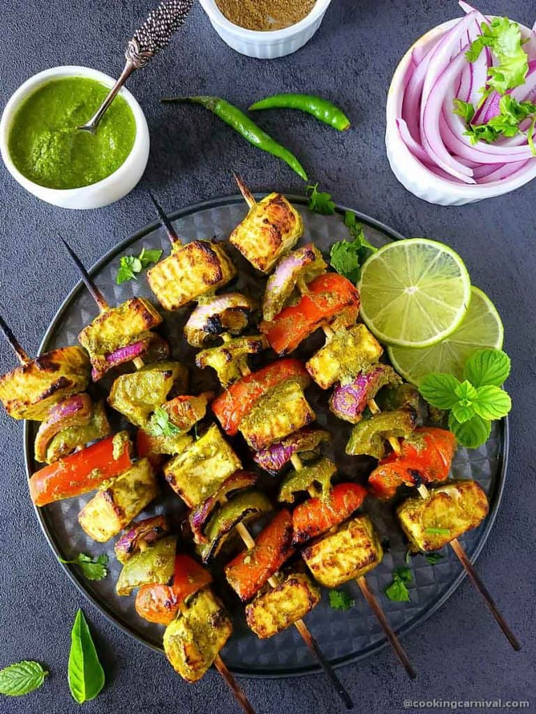Hariyali Paneer Tikka on a baking tray, green chuntey, lime, chaat masala and onion on side