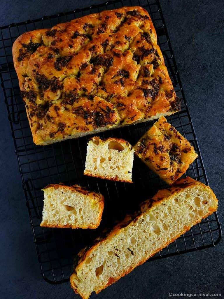 pieces of no knead pesto focaccia bread on gray board
