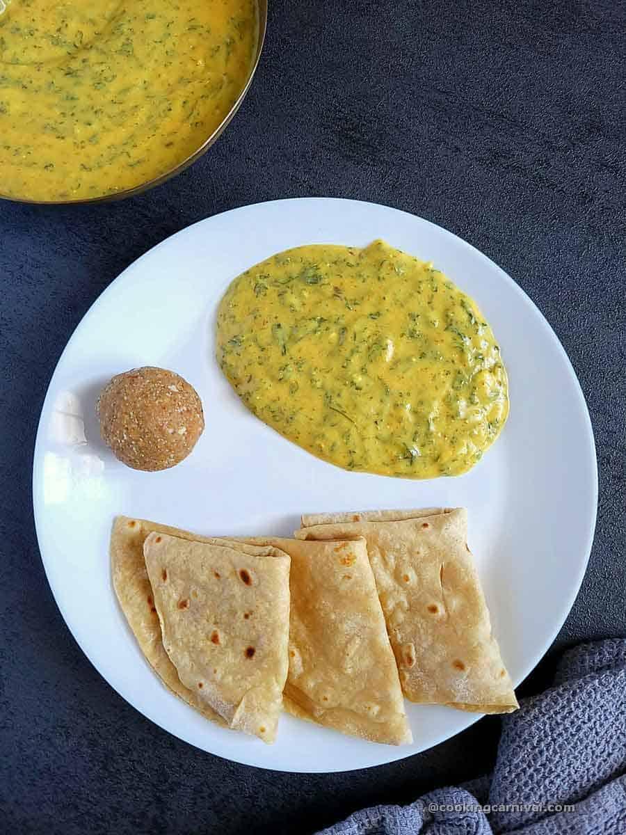 Methi Chana Na Lot No Ghegho, rotil and ladoo in a white plate