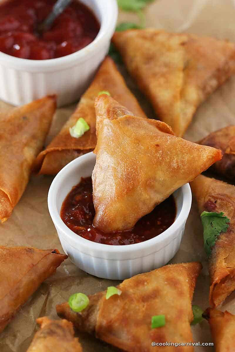 dipping noodle samosa in schezwan sauce